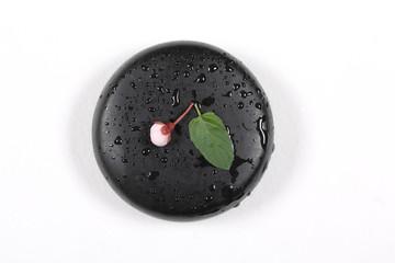 камни чёрные для массажа лежат на белом столе