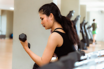 Portrait of asian woman lifting dumbbells in fitness gym., Sport and healthy concept