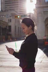 Woman using mobile phone while having drink