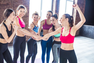 It was a cool workout. Smiling group of women friends in sportswear laughing and have a fun together in a gym after a workout