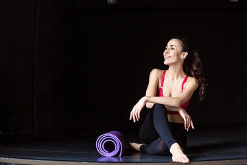 Rest after workout in the gym. Sport beautiful smiling woman in sportswear with a yoga mat sitting...
