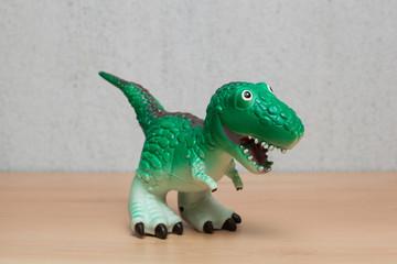 Tyrannosaurus dinosaurs toy on wooden table.
