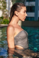 side view of attractive wet young woman in swimming pool