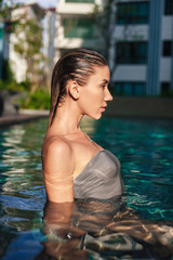 side view of seductive wet young woman in swimming pool