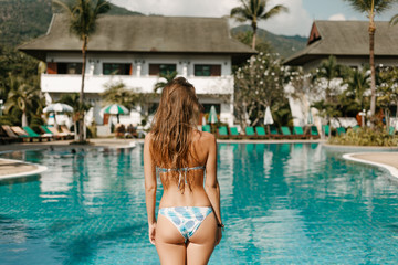 back view of slim girl posing in swimsuit at swimming pool Wall mural