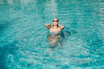 girl posing in swimsuit and sunglasses in swimming pool