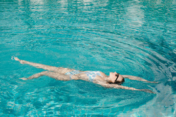 attractive girl in sunglasses swimming in pool