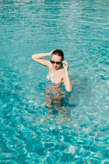 woman posing in sunglasses in swimming pool
