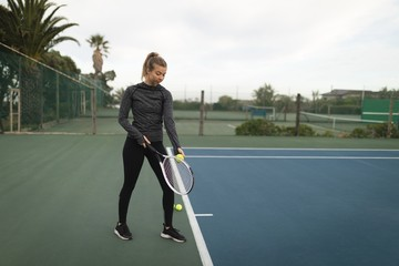 Woman practising tennis in tennis court