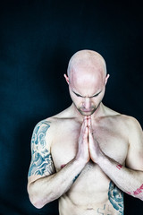 Muscular man performs Yoga and meditation