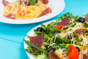 Close up of delicious salad in white plate on blue wooden table, spaghetti in the background