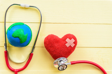 World health day, Healthcare and medical concept. Red heart with Stethoscope and handmade globe on Pastel white and yellow wooden background.