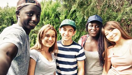 Multi ethnic teenagers smiling outdoor making selfie