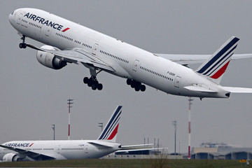 An Air France Boeing 777 airplane takes off past a control tower at the Charles-de-Gaulle airport in Roissy, near Paris