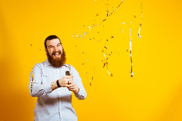 Portrait of Screaming bearded hipster man throwing confetti over yellow background, copyspace, free space for text. Businessman throwing confetti in the air.