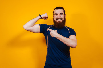 Cheerful bearded fitness man pointing at his biceps