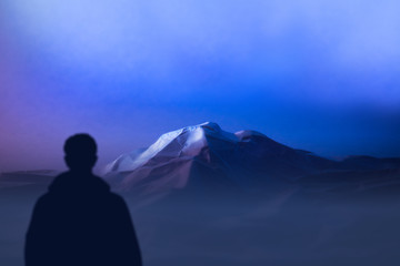 silhouette climber stands at foot mountains watching of mountain top. expedition to Himalayas evening landscape