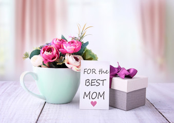 """Happy mothers day gifts with red white roses in a cup, and gift tag with text """"For the best mom"""", presented on wooden table with bright backround"""