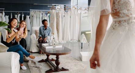 Friends with bride in bridal dress fitting room