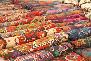 Bright colored fabrics India ornaments and oriental drawings. It is built on the market. Hand Embroidery India. Tablecloths of different colors are sold at the bazaar in India, Goa