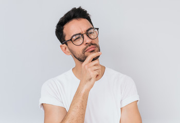 Portrait of thoughtful bearded man wearing white T-shirt, looks pensively aside, thinks about his actions and plans for new projects, posing on white studio wall background. People and emotion concept