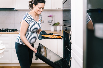 portrait of pregnant woman preparing pizza at home