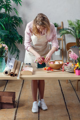 Picture of florist woman in apron with marshmallow, marmalade at table