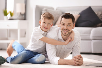 Little boy and his dad spending time together at home