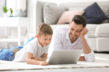 Little boy and his dad using laptop at home
