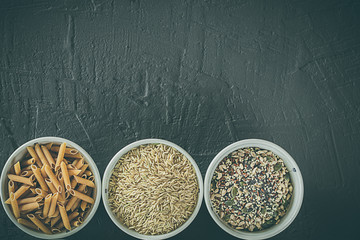 Brown rice grains, seeds and whole grain pasta in a bowl. Healthy food. Space for writing
