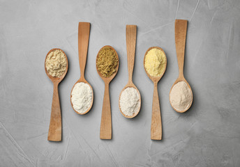 Spoons with different types of flour on gray background
