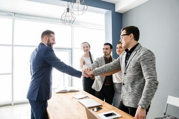 Handshake of two business partners in the team