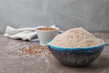 Bowl with buckwheat flour on table
