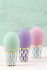 Three Easter eggs of pastel color on retro stands..