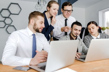 Group of businessmen working with a laptop denouncing investing
