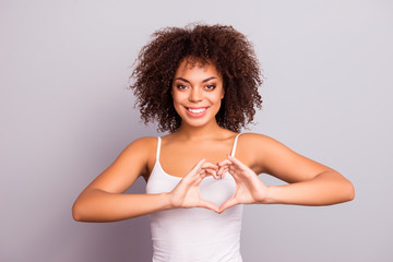 Portrait of charming cheerful pretty cute sweet attractive brunette girl sending love symbol, making heart figure with fingers, looking at camera, isolated on grey background