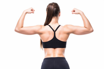 Athletic young woman showing muscles of the back and hands on isolated white background