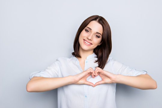 Portrait of pretty, charming, stylish, modern, cute, brunette woman with hairstyle in shirt showing love symbol, heart shape with fingers, looking at camera, isolated on grey background