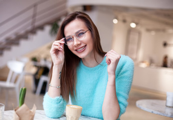 Gorgeous smiling young woman looking straight at camera while drinking coffee in a cafe