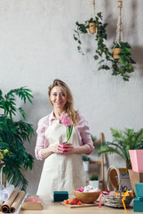 Image of florist blonde in apron at room with flowers