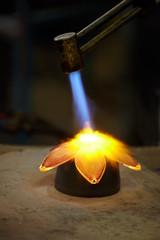 Glass-blower burns glass flower