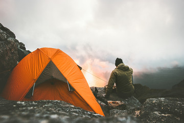 Photo sur Plexiglas Camping Man traveler alone enjoying sunset in mountains sitting near of tent camping gear outdoor Travel adventure lifestyle concept hiking wanderlust vacations