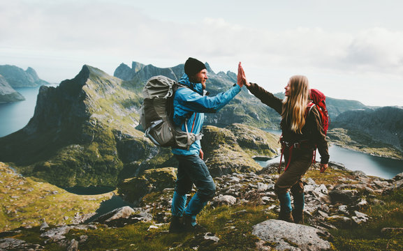 Happy couple giving five hands hiking with backpack in mountains Travel lifestyle adventure concept family together spending active wanderlust vacations
