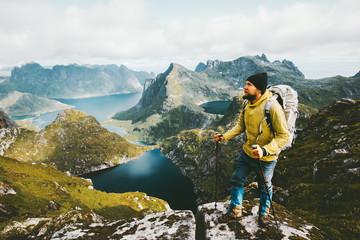 Bearded man traveler standing on cliff mountain in Norway Traveling with backpack healthy lifestyle adventure concept hiking active summer vacations outdoor Wall mural