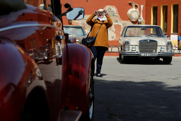 A woman takes a pictures of the cars after the owners of vintage cars and their familes made a tour in through the streets of Amman
