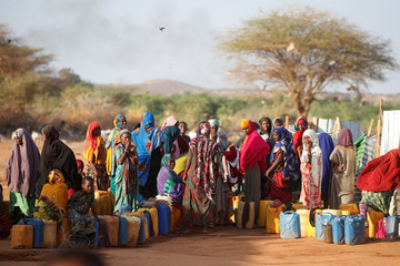 Somali women wait to collect water at the New Kabasa Internally displaced camp in the northern Somali town of Dollow