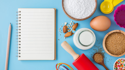 Baking ingredients and utensils with blank recipe book