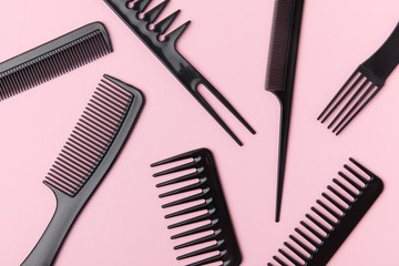 top view of black combs, isolated on light pink