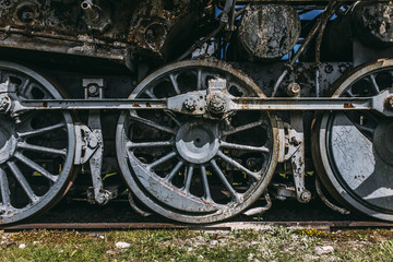 Close up of a steam locomotives iron wheels on a rail track