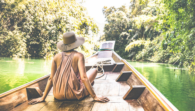 Young woman traveler on longtail boat trip at island hopping in Cheow Lan Lake - Wanderlust and travel concept with adventure girl tourist wanderer on excursion in Thailand - Warm greenish filter
